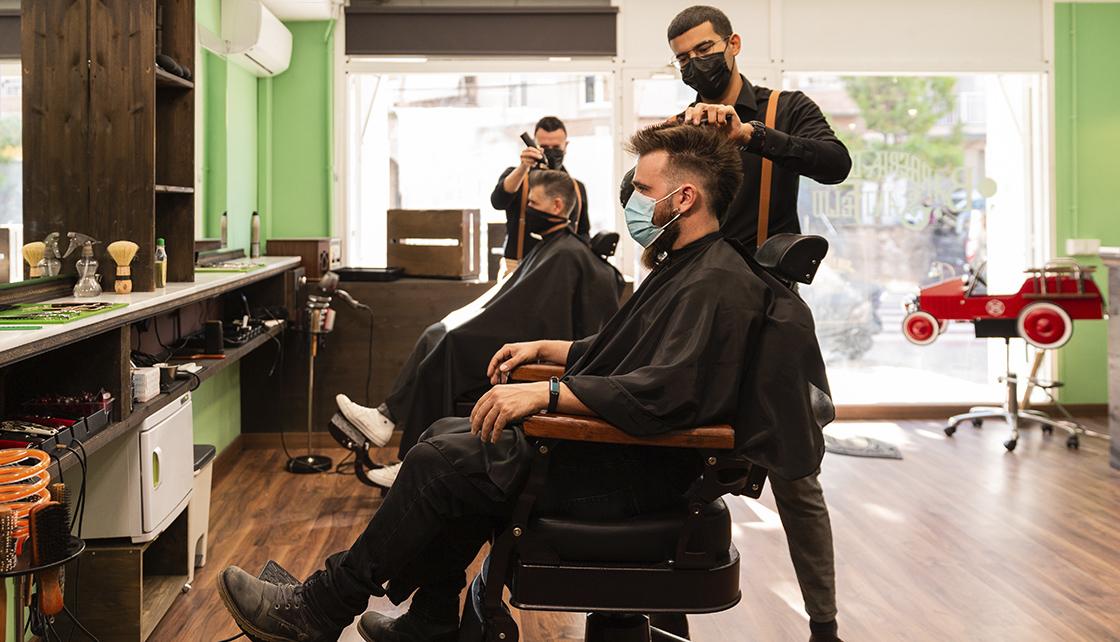 Em uma barbearia, cliente e profissional aparecem em primeiro plano