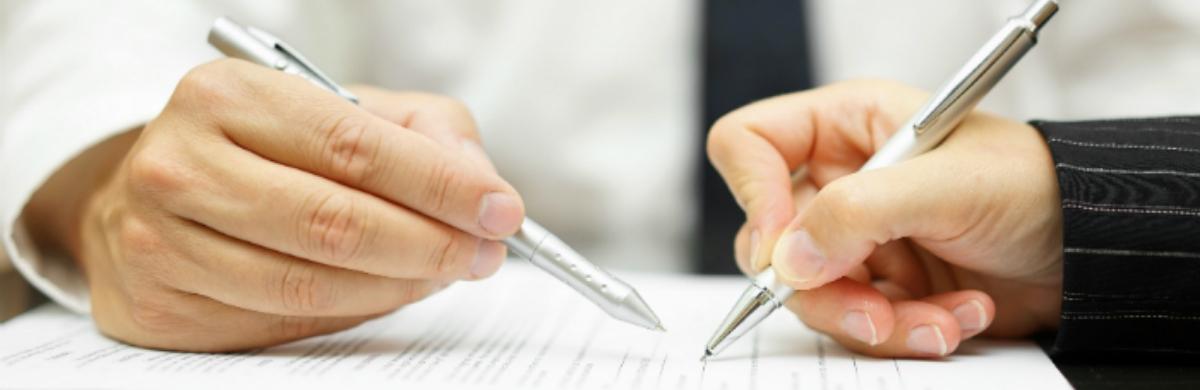Detalhe de mãos sobre documento sendo assinado sobre a mesa