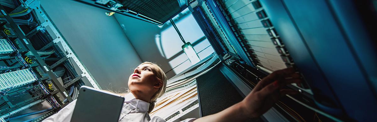 Mulher opera equipamentos em data center