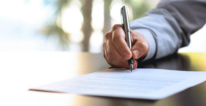 Detalhe de mão assinando documento