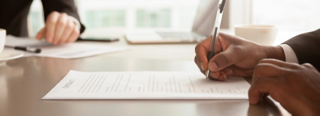 Detalhe de mãos de homem assinando papel sobre a mesa