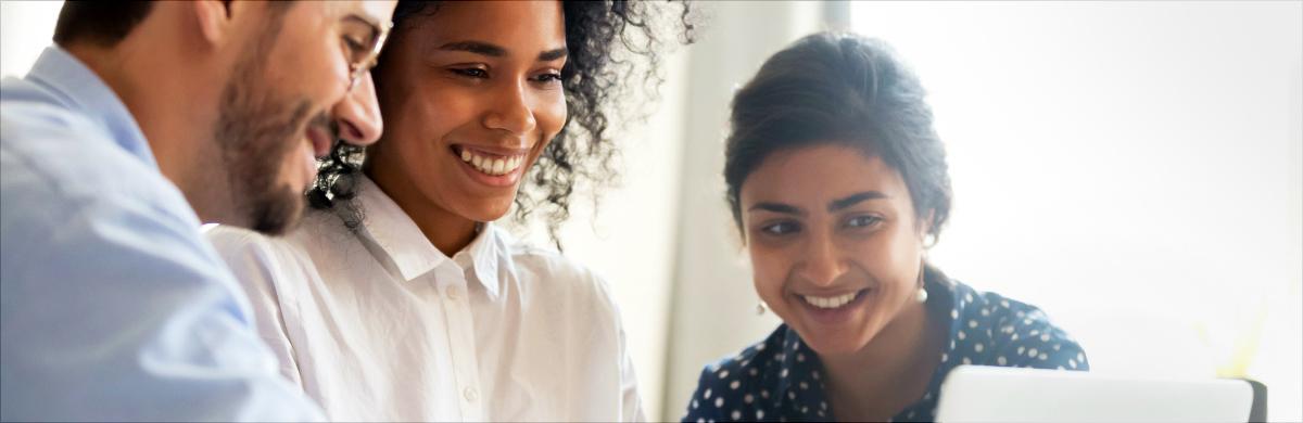 Imagem de um homem e duas mulheres olhando tela de computador