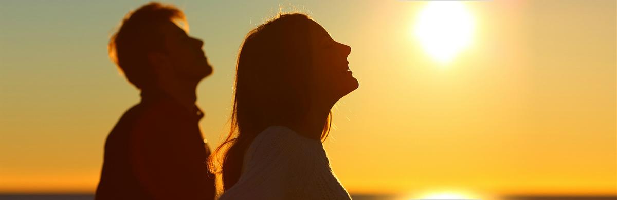 Homem e mulher de perfil com pôr do sol ao fundo