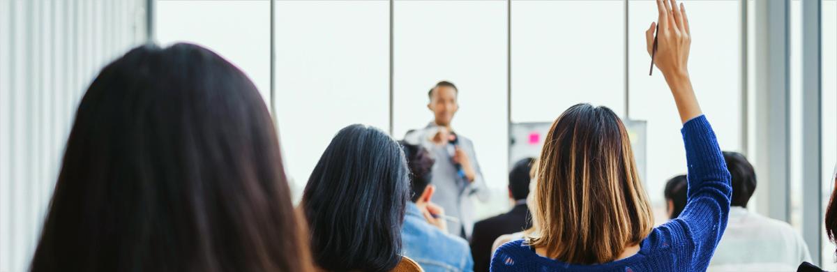 Imagem de pessoa levantando a mão para tirar dúvida durante treinamento