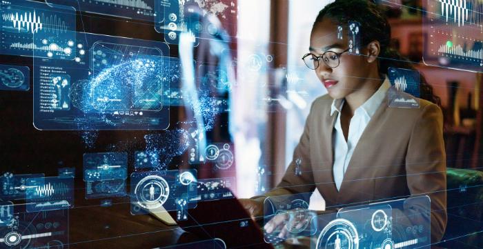 Imagem de mulher à frente de computador, com imagens abstratas que remetem à tecnologia à frente