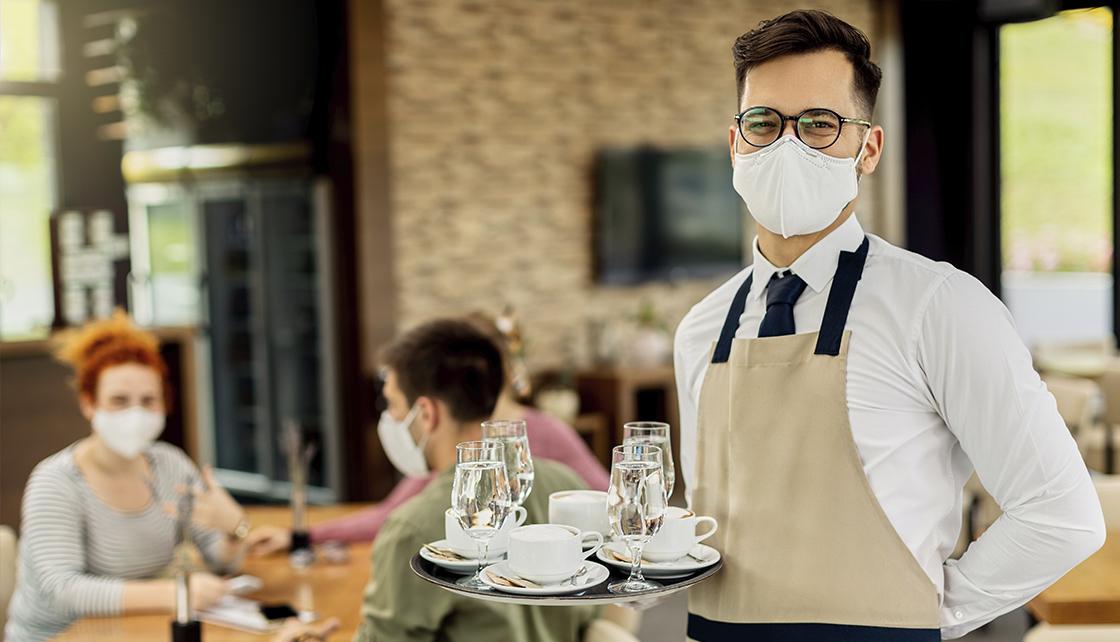 Em primeiro plano, garçom com avental e máscara posa para foto