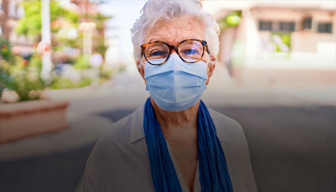 Uma senhora de cabelos brancos e usando máscara azul posa para foto